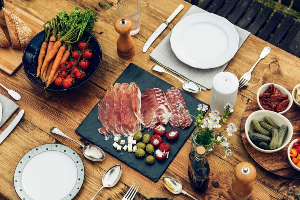Platter of ham and salami with vegetables, on a wooden table. The Best Restaurants in Las Palmas. Experience the best food in Las Palmas de Gran Canaria. Article by https://www.kissmybackpack.com