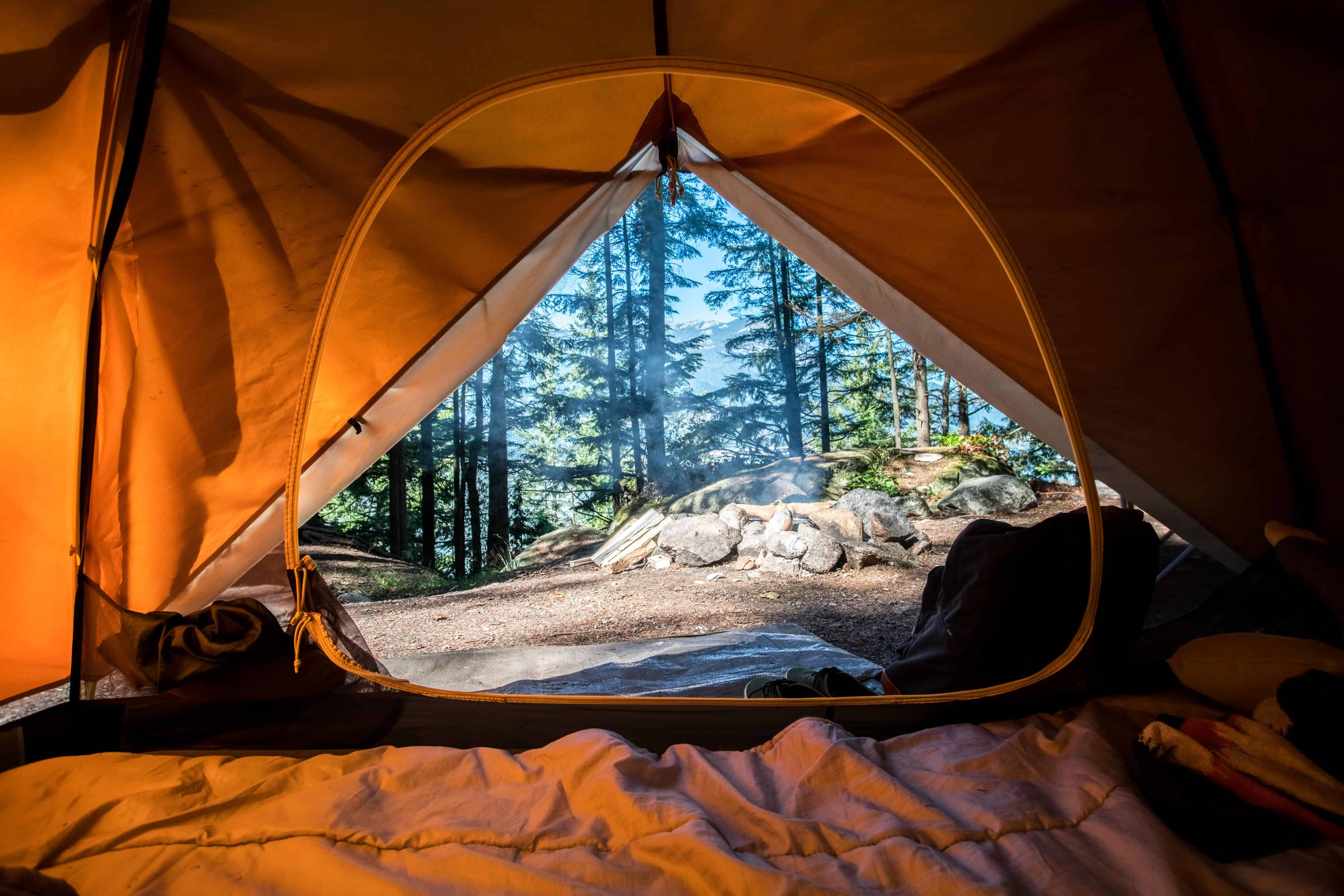 The inside of a tent with a beautiful forest just outside. It's time to hit the road! Destinations, guides, budget and luxury travel by https://www.kissmybackpack.com