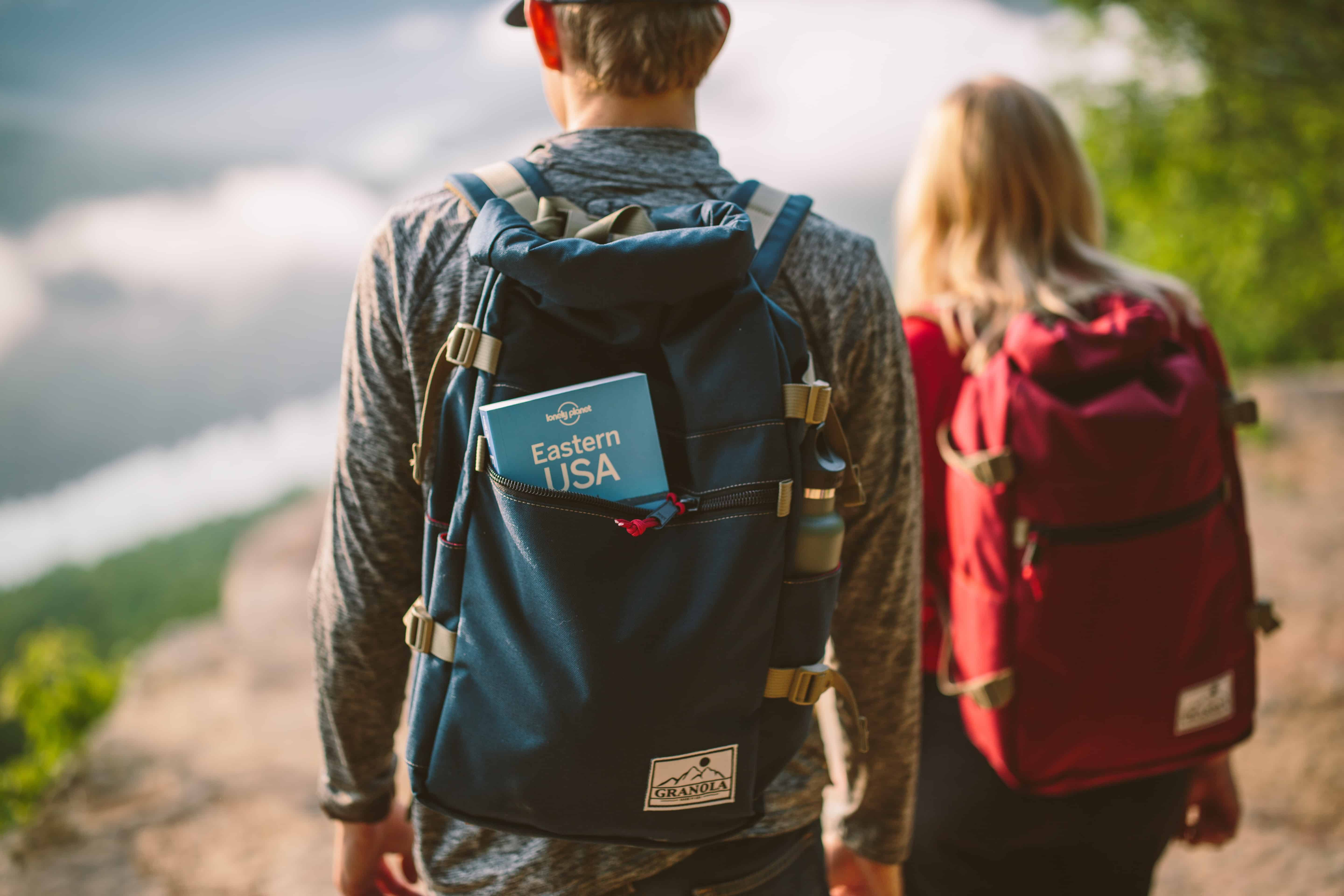 A hiking couple with a travel guide showing from a backpack. It's time to hit the road! Destinations, guides, budget and luxury travel by https://www.kissmybackpack.com