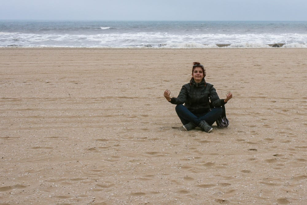 A girl meditating on a sandy beach in the Hague, The Netherlands