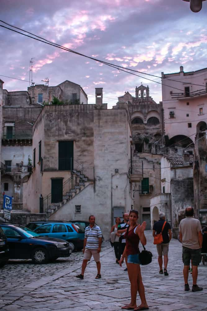 How to travel as a student: A girl exploring the narrow streets and elevated cave buildings in Matera, Italy during a colourful sunset