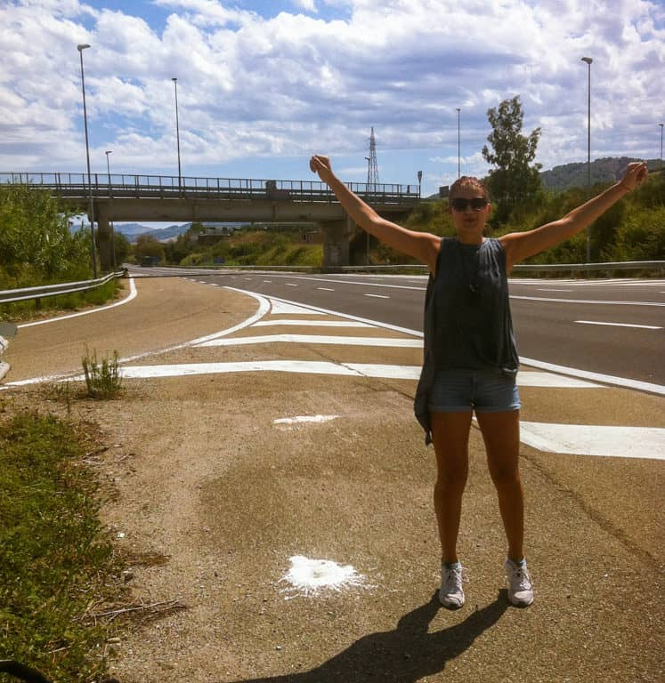 A happy hitchhiker girl in the middle of nowhere