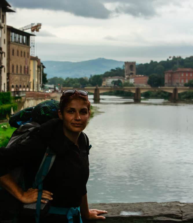 A travelling student with a backpack standing on a bridge on the Arno River in Florence, Italy