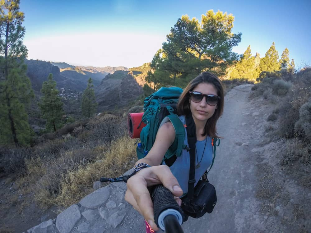 Tips on how to travel as a student: A girl camping alone overnight, taking a morning walk in the mountains in Gran Canaria, Spain