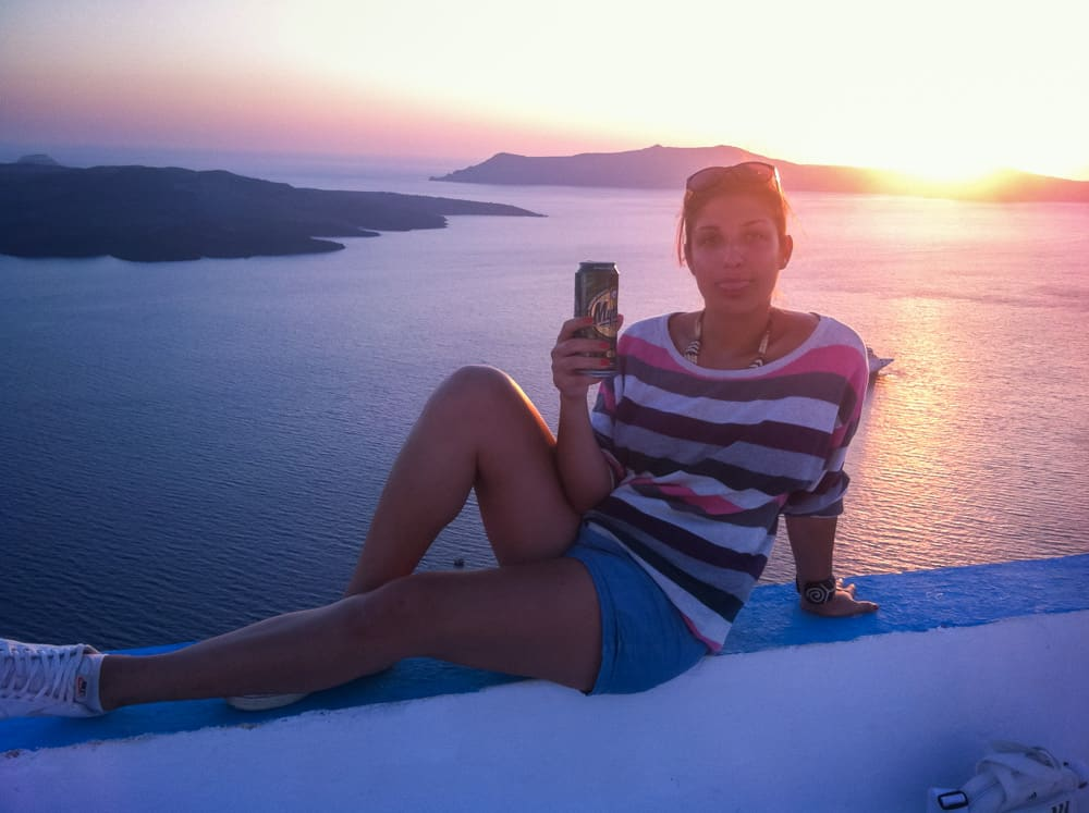 A girl enjoying a can of beer during a stunning pink sunset over the ocean in the island of Santorini in Greece