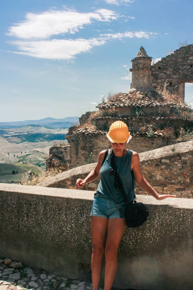 A girl with a protection hat exploring the ruins of the ghost town of Craco in Basilicata in the south end of Italy