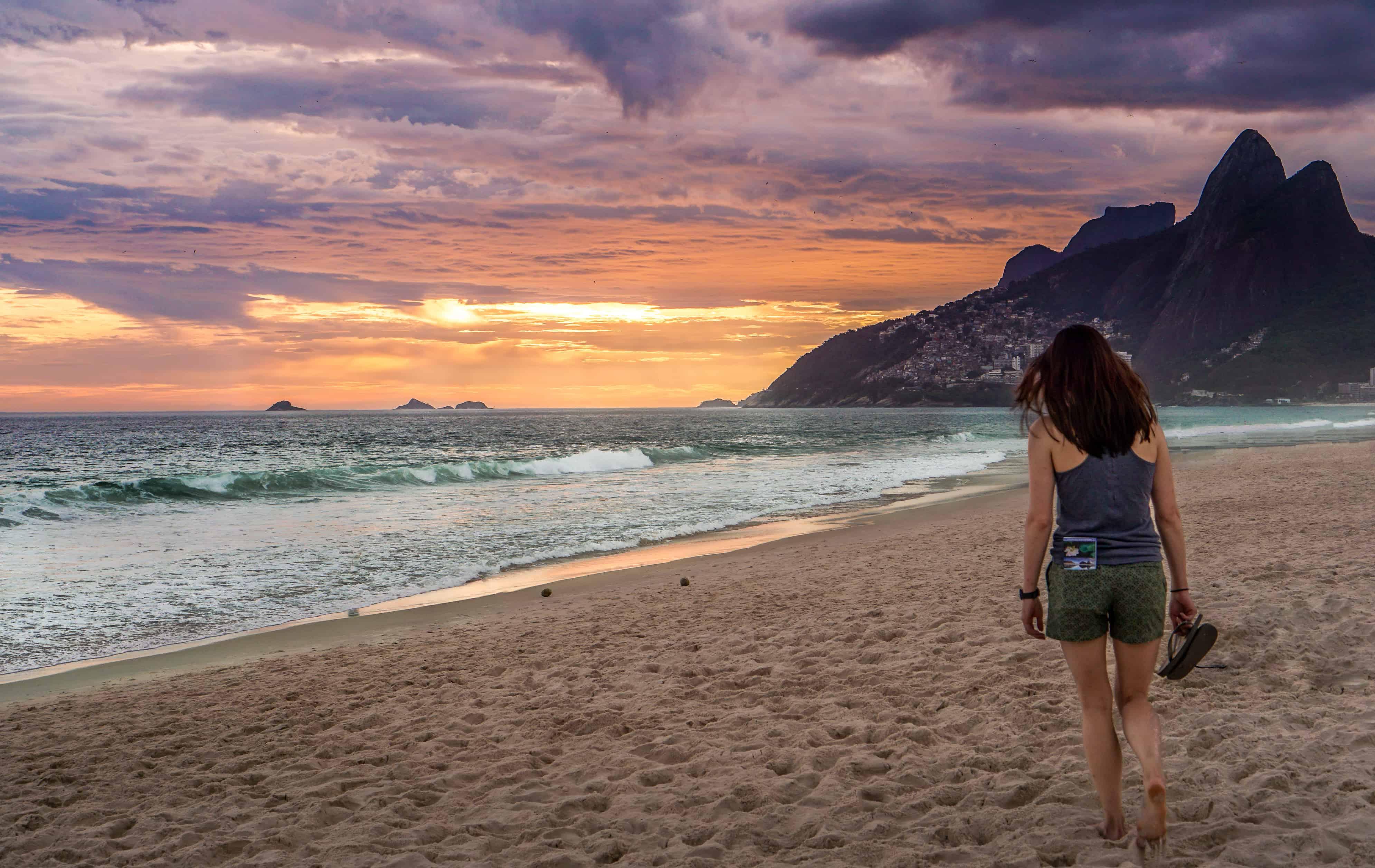 A woman walking on the beach towards the beautiful sunset in Rio de Janeiro