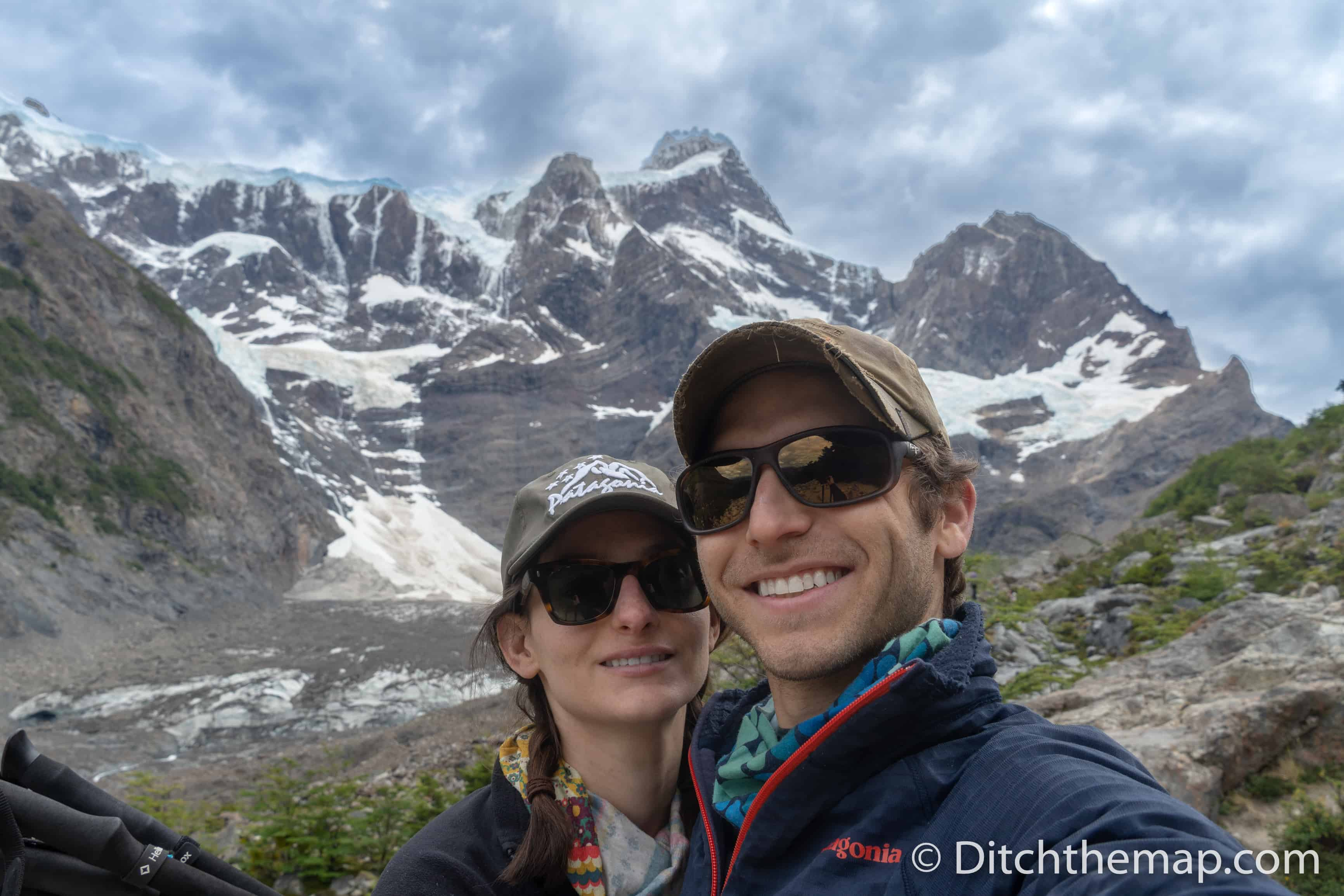 A couple's selfie in front of Torres del Paine Trek snowy mountains