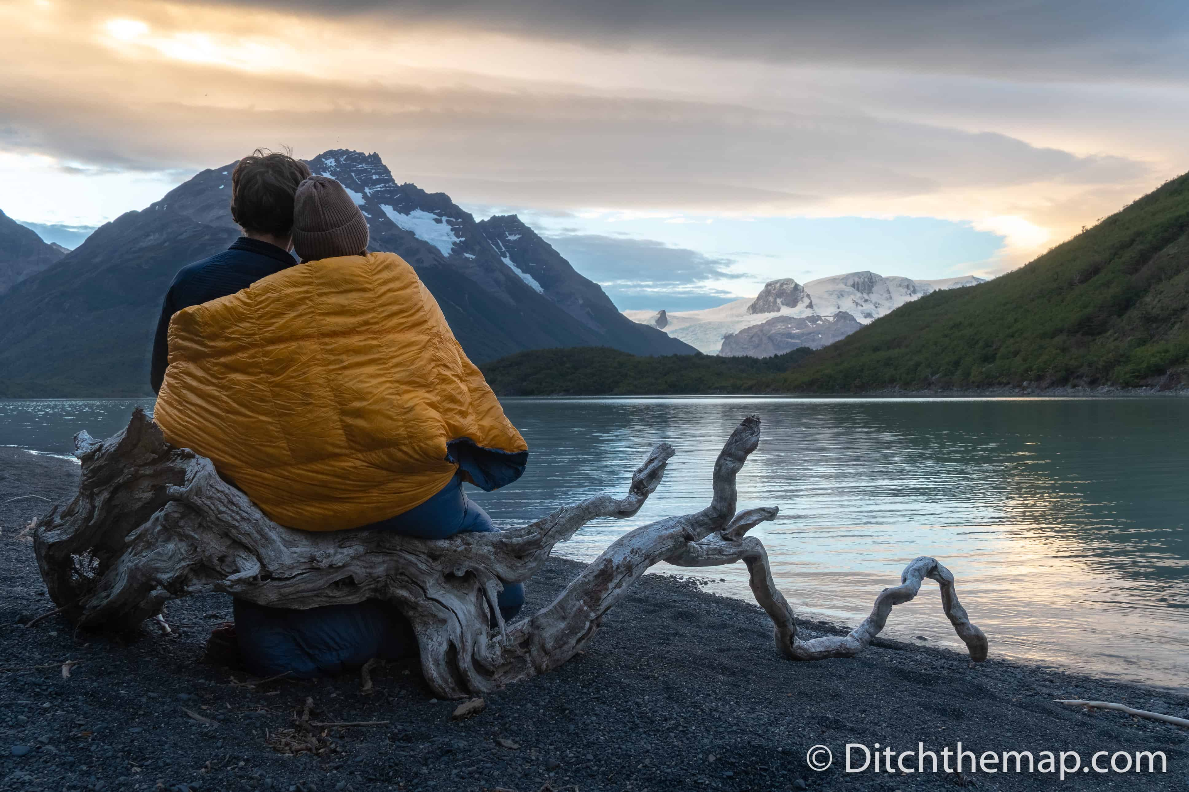 A couple keeping warm with a sleeping bag next to a cold lake and mountain view