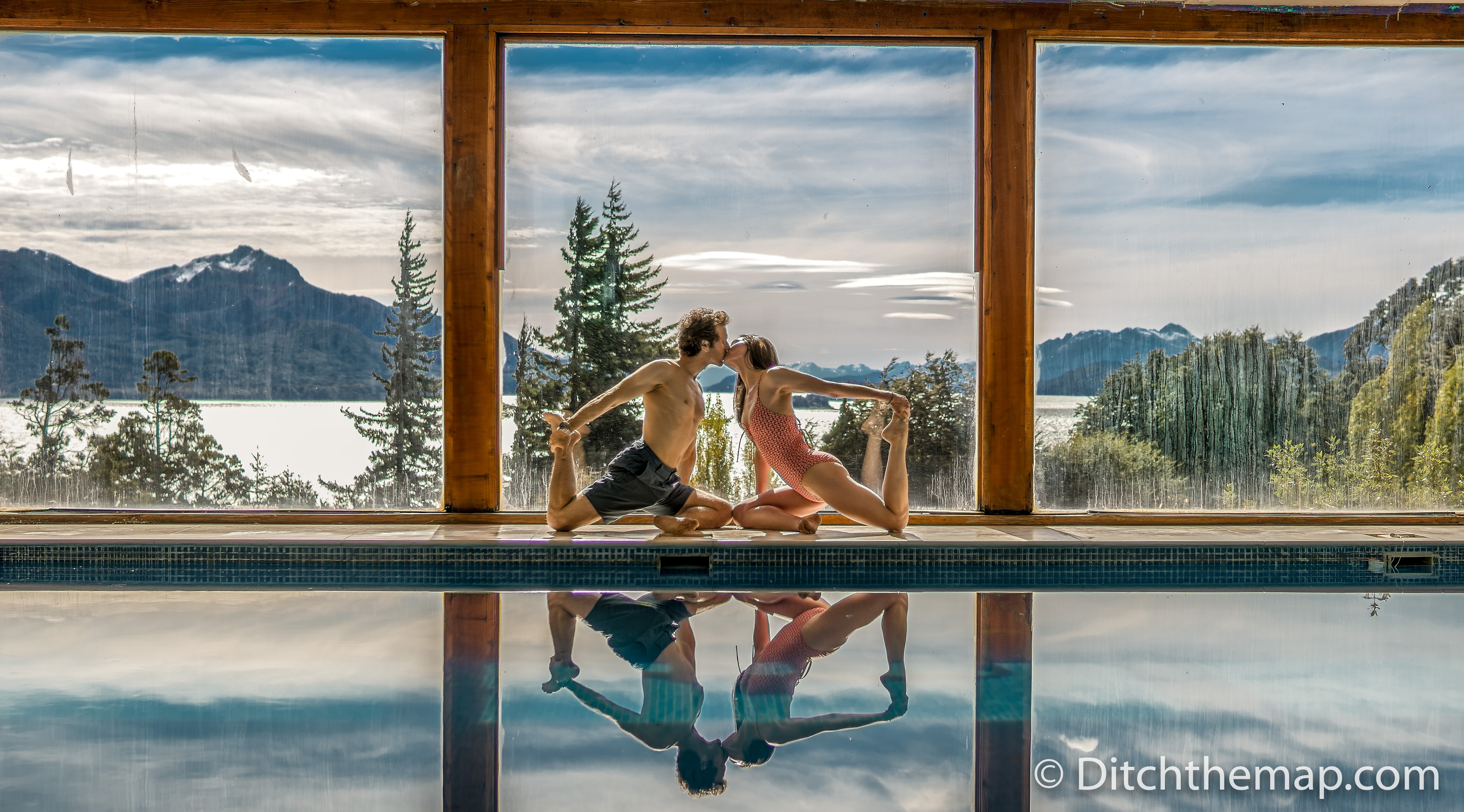 A man and a woman kissing while in a yoga pose next to a pool with a mountain landscape