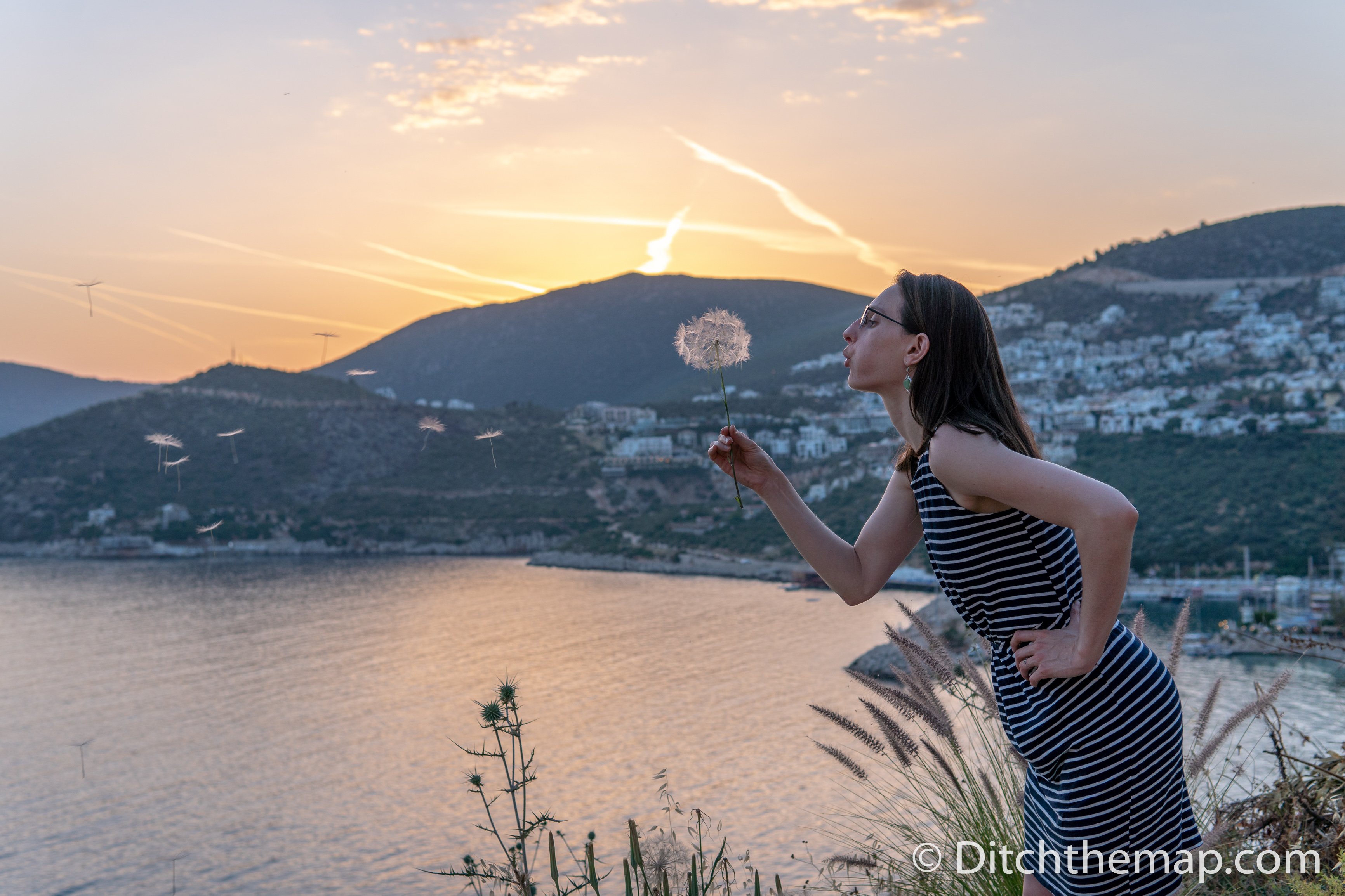 A girl blowing a dandelion during sunset next to a lake and mountains