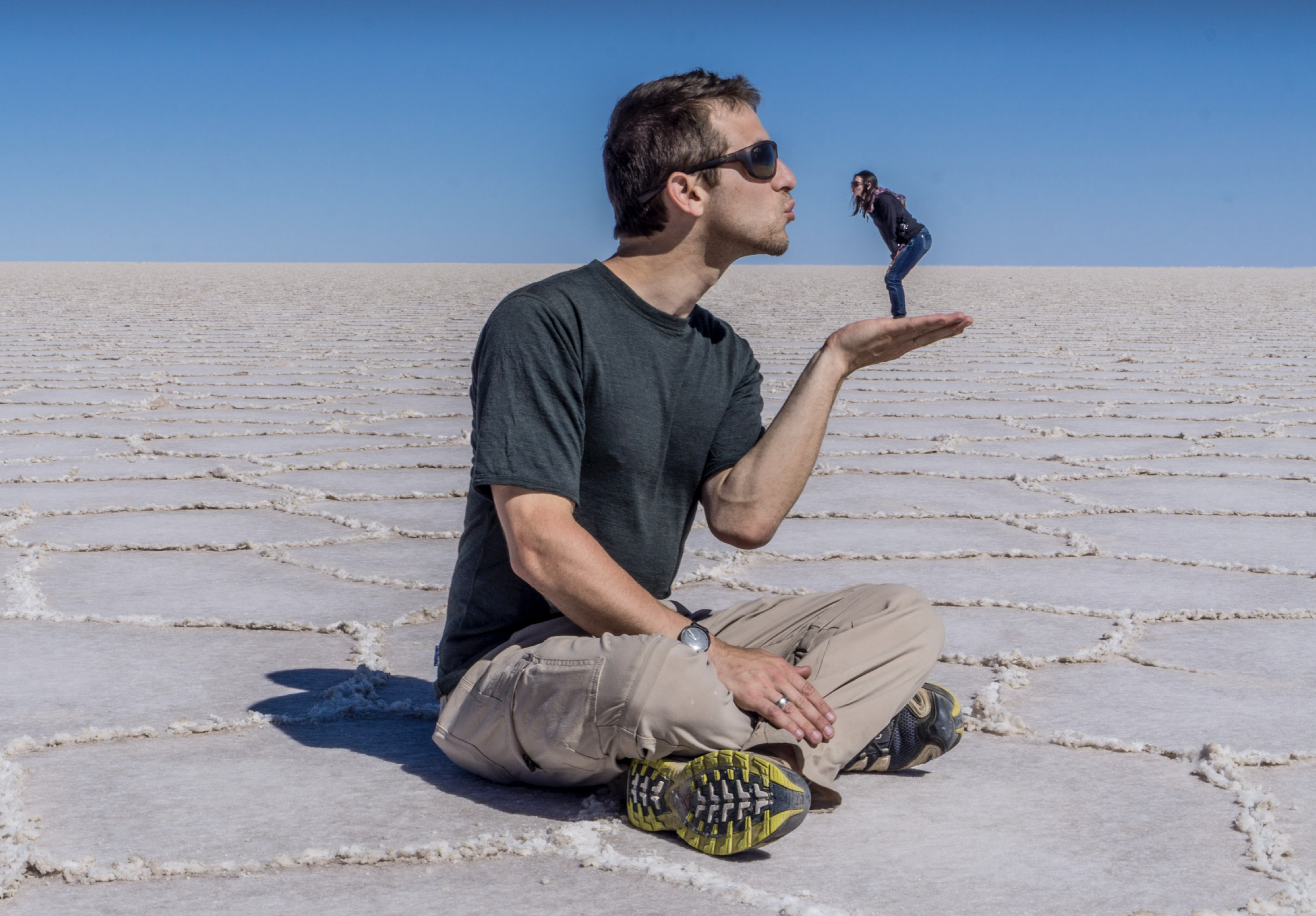 A big man holding and kissing a tiny woman in his hand in the salt lakes