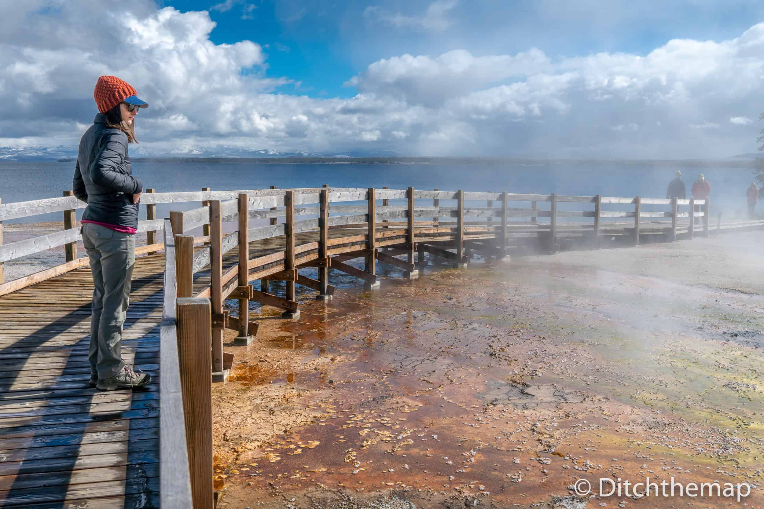 A woman with a jacket looking at the steam coming from the ground at Yellowstone