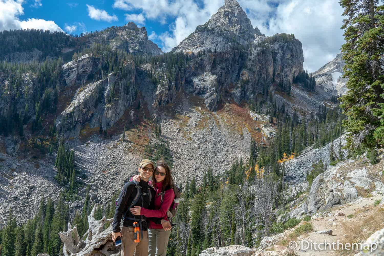 A hiking couple's photo in front of high-peaked mountain, the Grand Tetons