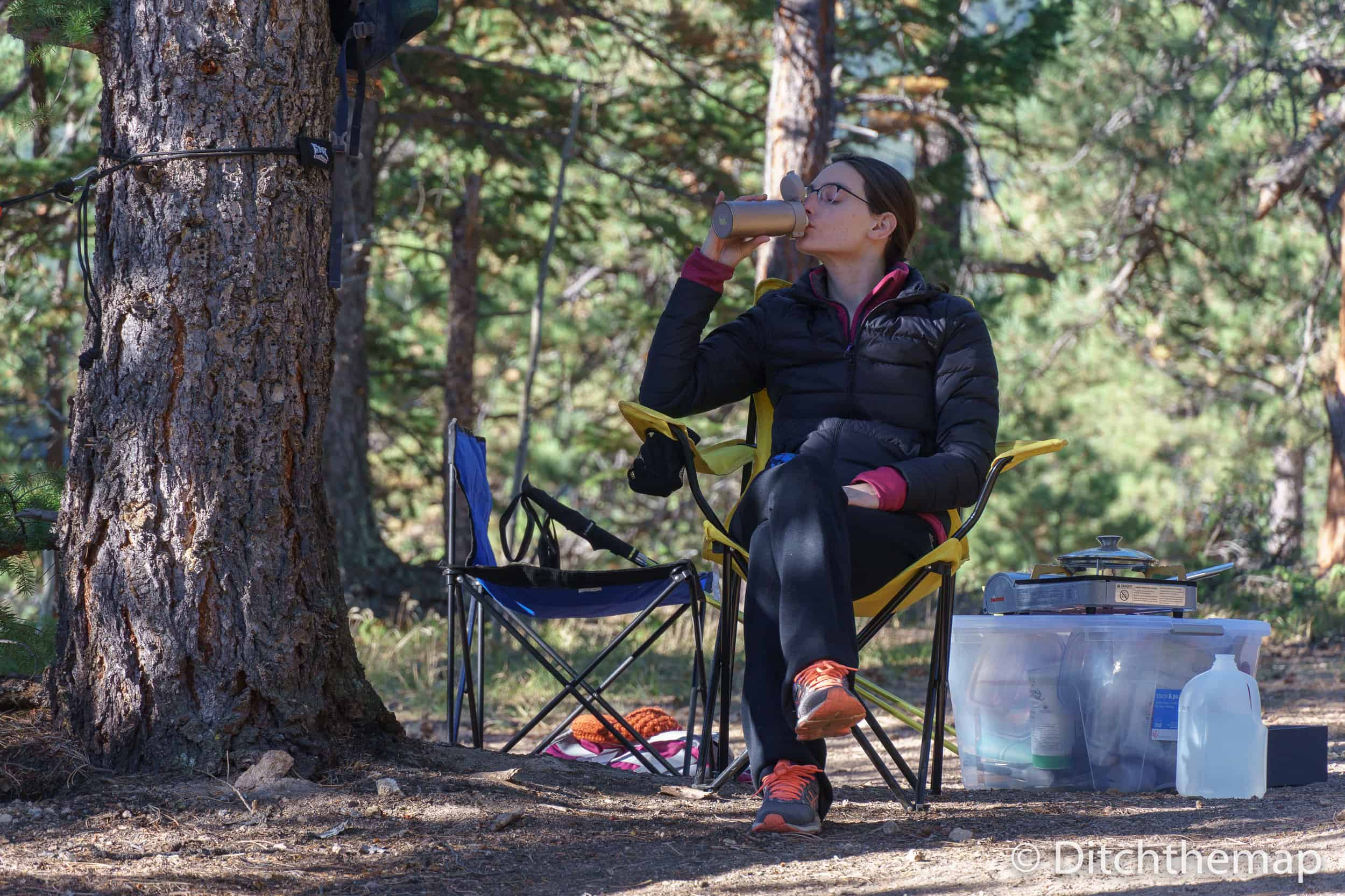 A woman enjoying her cup of tea while camping in the forest