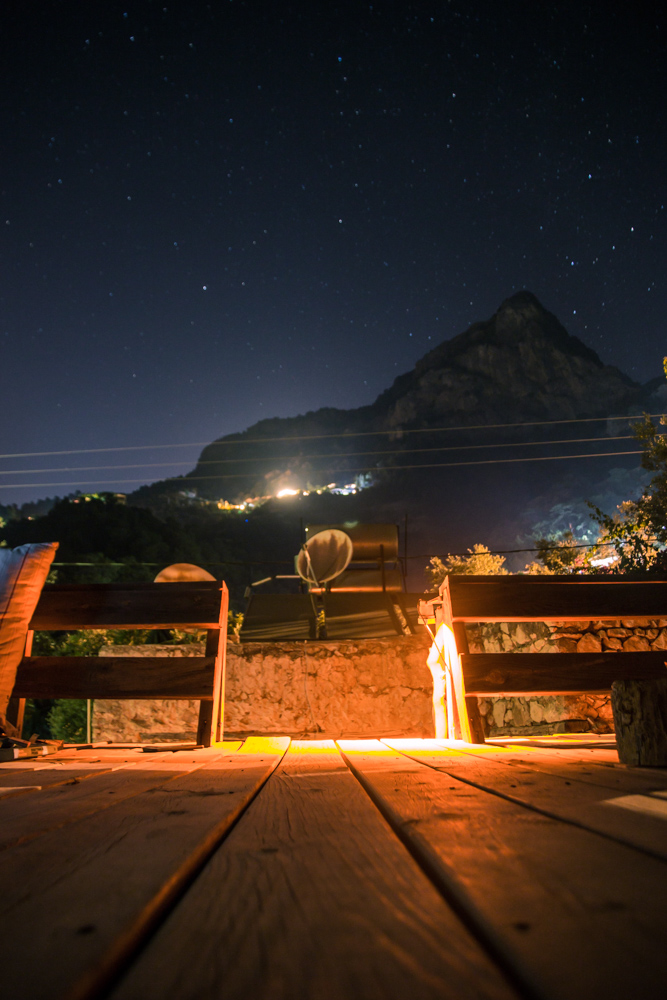 View from the wooden rooftop area at night. Clear sky with lots of stars, cozy warm light from the rooftop, view towards the mountain.